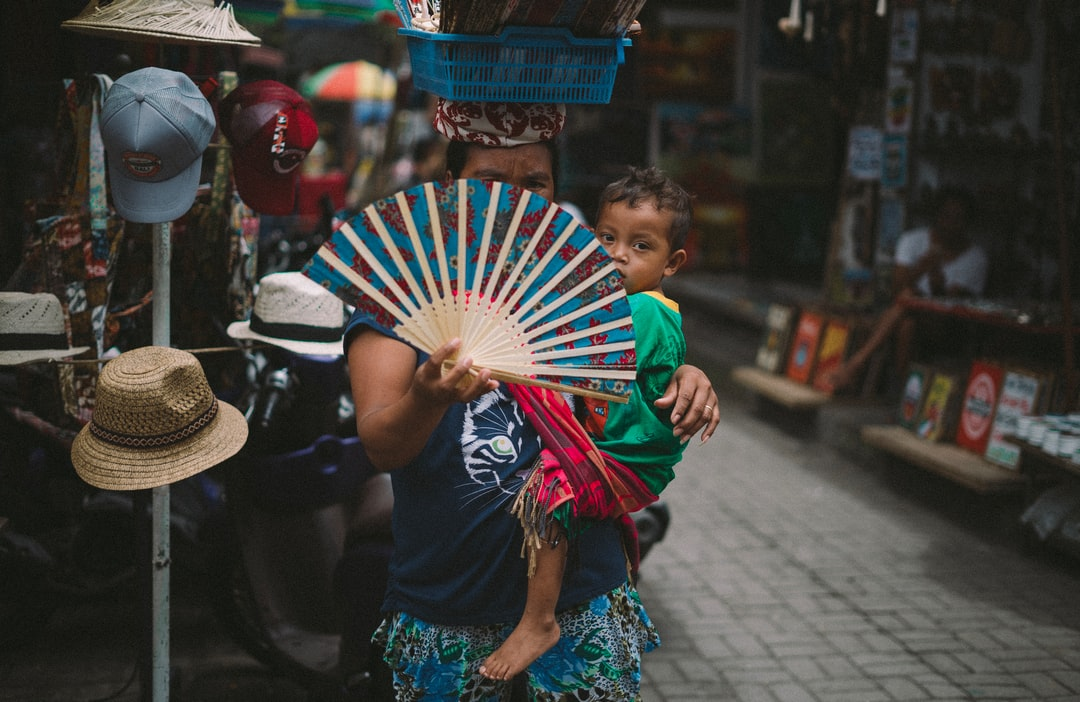 A small child is holding an umbrella