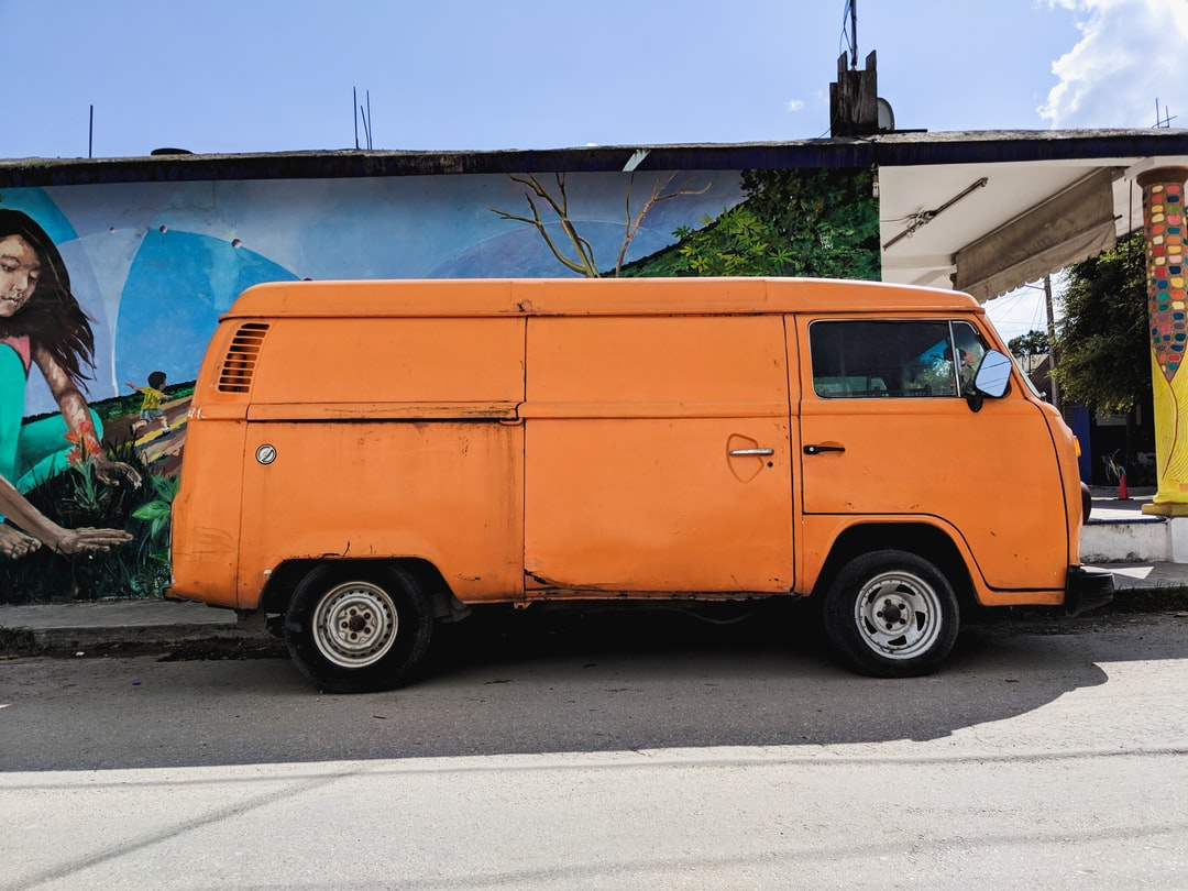 An orange truck parked in front of a building